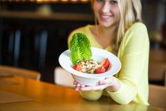 Όμορφο νέο κορίτσι που τρώει τη σαλάτα στον καφέ Στοκ Εικόνες