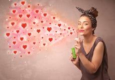 Όμορφο νέο κορίτσι που φυσά τα κόκκινα σύμβολα καρδιών Στοκ εικόνες με δικαίωμα ελεύθερης χρήσης