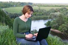 Όμορφο νέο κορίτσι που χρησιμοποιεί τη συνεδρίαση γραφικών ταμπλετών της στη χλόη Στοκ Φωτογραφίες