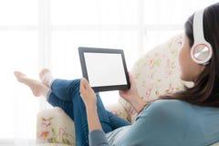 Όμορφο νέο κορίτσι που χρησιμοποιεί τον κινητό υπολογιστή μαξιλαριών Στοκ Εικόνα