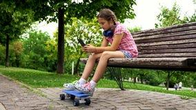 Όμορφο νέο κορίτσι σε έναν πάγκο στο παιχνίδι πάρκων στο smarphone της φιλμ μικρού μήκους