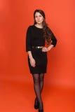 Όμορφο νέο κορίτσι σε ένα επιχειρησιακό κοστούμι σε ένα κόκκινο υπόβαθρο Στοκ Εικόνα