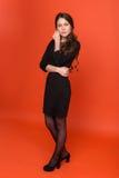 Όμορφο νέο κορίτσι σε ένα επιχειρησιακό κοστούμι σε ένα κόκκινο υπόβαθρο Στοκ φωτογραφία με δικαίωμα ελεύθερης χρήσης