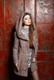 Όμορφο νέο κορίτσι σε ένα παλτό με την κουκούλα κοντά στον εκλεκτής ποιότητας τοίχο Στοκ Εικόνα