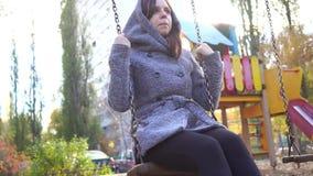 Όμορφο νέο κορίτσι σε ένα παλτό που ταλαντεύεται σε μια ταλάντευση απόθεμα βίντεο