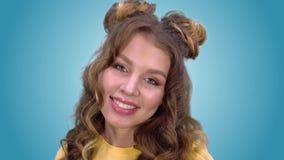 Όμορφο νέο κορίτσι σε μια καλή διάθεση που χαμογελά εξετάζοντας τη κάμερα E απόθεμα βίντεο