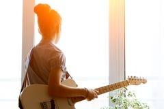 Όμορφο νέο κορίτσι σκιαγραφιών με την κιθάρα Στοκ φωτογραφία με δικαίωμα ελεύθερης χρήσης