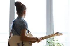 Όμορφο νέο κορίτσι σκιαγραφιών με την κιθάρα Στοκ Εικόνες