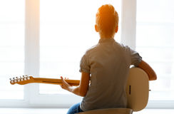 Όμορφο νέο κορίτσι σκιαγραφιών με την κιθάρα Στοκ Φωτογραφία