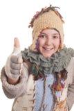 Όμορφο νέο κορίτσι στα θερμά χειμερινά ενδύματα που παρουσιάζουν αντίχειρα Στοκ φωτογραφίες με δικαίωμα ελεύθερης χρήσης
