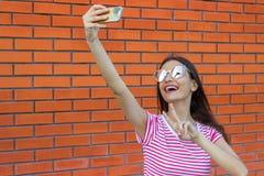 Όμορφο νέο κορίτσι στα ρόδινα γυαλιά ηλίου που κάνουν selfie και που παρουσιάζουν δύο δάχτυλα πέρα από το υπόβαθρο τουβλότοιχος Στοκ Εικόνες
