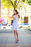Όμορφο νέο κορίτσι στην άσπρη θερινή οδό περπατήματος φορεμάτων Στοκ Φωτογραφίες