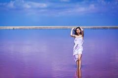 Όμορφο νέο κορίτσι στην πολύ άσπρη τοποθέτηση φορεμάτων στην αλμυρή ρόδινη λίμνη στοκ εικόνες με δικαίωμα ελεύθερης χρήσης