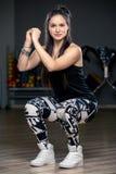 όμορφο νέο κορίτσι στη γυμναστική που κάνει τη στάση οκλαδόν Στοκ Φωτογραφίες