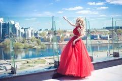 Όμορφο νέο κορίτσι στη στέγη ενός κτηρίου σε ένα κόκκινο πολύβλαστο φόρεμα στοκ φωτογραφία με δικαίωμα ελεύθερης χρήσης