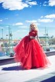Όμορφο νέο κορίτσι στη στέγη ενός κτηρίου σε ένα κόκκινο πολύβλαστο φόρεμα στοκ εικόνες
