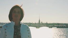 Όμορφο νέο κορίτσι στο άσπρο σακάκι στη στέγη με τη φυσική άποψη ποταμών πόλεων απόθεμα βίντεο