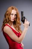 Όμορφο νέο κορίτσι στο κόκκινο φόρεμα με το πυροβόλο όπλο στοκ φωτογραφίες