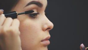 Όμορφο νέο κορίτσι στο μαύρο υπόβαθρο Η χρήση του σφαγίου για τα eyelashes, του προσώπου ομορφιά, καθαρό δέρμα, αποτελεί τις έννο απόθεμα βίντεο