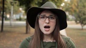 Όμορφο νέο κορίτσι στο πάρκο φθινοπώρου, οι συγκινήσεις της, ενόχληση, όχι ικανοποίηση απόθεμα βίντεο
