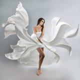 Όμορφο νέο κορίτσι στο πετώντας άσπρο φόρεμα Στοκ Φωτογραφίες
