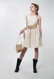 Όμορφο νέο κορίτσι στο σύγχρονο φόρεμα με το πορτοφόλι Στοκ φωτογραφία με δικαίωμα ελεύθερης χρήσης