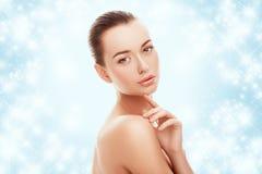 Όμορφο νέο κορίτσι σχετικά με το πρόσωπό της στο μπλε υπόβαθρο και το χιόνι Έννοια πλαστικής χειρουργικής, λίφτινγκ και αναζωογόν στοκ εικόνες