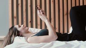 Όμορφο νέο να βρεθεί γυναικών στο κρεβάτι και κάνει σερφ το Διαδίκτυο στην κρεβατοκάμαρα smartphone στο σπίτι Θηλυκό κινητό τηλέφ φιλμ μικρού μήκους