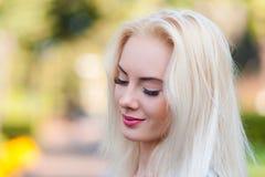 Όμορφο νέο ξανθό κορίτσι με ένα όμορφο πρόσωπο και όμορφα μάτια χαμόγελου Το πορτρέτο μιας γυναίκας με μακρυμάλλη και την κατάπλη Στοκ εικόνα με δικαίωμα ελεύθερης χρήσης
