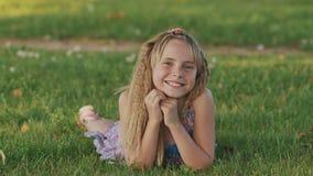 Όμορφο νέο ξανθό κορίτσι που βρίσκεται σε έναν τομέα, πράσινη χλόη Υπαίθρια απολαύστε τη φύση Υγιές χαμογελώντας κορίτσι που βρίσ απόθεμα βίντεο