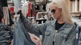 Όμορφο νέο ξανθό κορίτσι που επιλέγει τα τζιν στο κατάστημα φιλμ μικρού μήκους