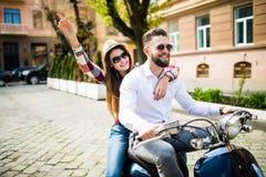 Όμορφο νέο οδηγώντας μηχανικό δίκυκλο ζευγών κατά μήκος μιας οδού και ενός χαμόγελου Στοκ Φωτογραφία