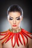 Όμορφο νέο πορτρέτο γυναικών με το κόκκινο - καυτά και πικάντικα πιπέρια Στοκ Εικόνες