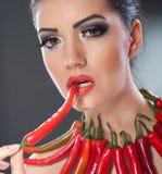 Όμορφο νέο πορτρέτο γυναικών με το κόκκινο - τα καυτά και πικάντικα πιπέρια, πρότυπο μόδας με το δημιουργικό λαχανικό τροφίμων απ στοκ φωτογραφία