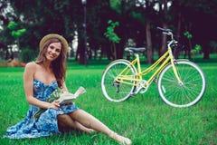 Όμορφο νέο πορτρέτο γυναικών που διαβάζει ένα βιβλίο με το ποδήλατο στο πάρκο στοκ εικόνες