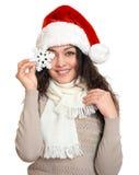 Όμορφο νέο πορτρέτο γυναικών στο καπέλο αρωγών santa με τη μεγάλη snowflake τοποθέτηση στο λευκό Στοκ Φωτογραφίες