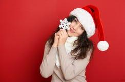 Όμορφο νέο πορτρέτο γυναικών στο καπέλο αρωγών santa με τη μεγάλη snowflake τοποθέτηση στο κόκκινο Στοκ Φωτογραφία