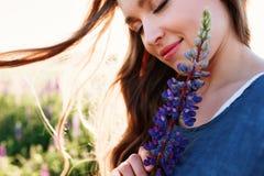 Όμορφο νέο πορτρέτο προσώπου γυναικών στον τομέα lupine, που κρατά το λουλούδι κοντά στο μάγουλο στοκ εικόνα με δικαίωμα ελεύθερης χρήσης