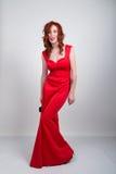 Όμορφο νέο προκλητικό λεπτό κοκκινομάλλες κορίτσι που φορά υψηλά τακούνια τα κρυψίνους μεταξιού κόκκινα φορεμάτων, στην οινοπνευμ Στοκ Φωτογραφία