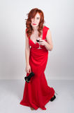 Όμορφο νέο προκλητικό λεπτό κοκκινομάλλες κορίτσι που φορά υψηλά τακούνια τα κρυψίνους μεταξιού κόκκινα φορεμάτων, στην οινοπνευμ Στοκ Φωτογραφίες