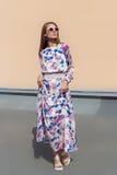 Όμορφο νέο προκλητικό κορίτσι στο κομψό φόρεμα σχεδιαστών φιαγμένο από ελαφρύ ύφασμα στα γυαλιά ηλίου που θέτουν στη κάμερα Στοκ φωτογραφίες με δικαίωμα ελεύθερης χρήσης