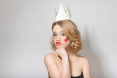 Όμορφο νέο πρότυπο κορίτσι με την κορώνα εγγράφου στο κεφάλι της, με μια καρδιά και τα φτυάρια στο πρόσωπό της Στοκ Φωτογραφία