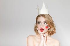 Όμορφο νέο πρότυπο κορίτσι με την κορώνα εγγράφου στο κεφάλι της, με μια καρδιά και τα φτυάρια στο πρόσωπό της Στοκ Εικόνες