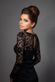 Όμορφο νέο πρότυπο στο μαύρο φόρεμα που στέκεται πίσω στη κάμερα Στοκ Εικόνες