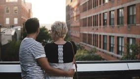 Όμορφο νέο ρομαντικό ζεύγος που στέκεται και που αγκαλιάζει σε μια γέφυρα την ομιλία, που απολαμβάνει καταπληκτικός το τοπίο πόλε φιλμ μικρού μήκους