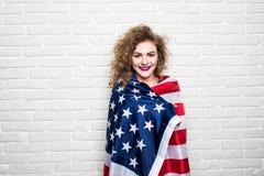 Όμορφο νέο σγουρό κορίτσι ενδύματα που θέτουν και που χαμογελούν, στάση που καλύπτεται στα περιστασιακά με τη αμερικανική σημαία  Στοκ εικόνα με δικαίωμα ελεύθερης χρήσης