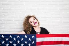 Όμορφο νέο σγουρό κορίτσι ενδύματα που θέτουν και που χαμογελούν, στάση που καλύπτεται στα περιστασιακά με τη αμερικανική σημαία  Στοκ φωτογραφίες με δικαίωμα ελεύθερης χρήσης