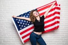 Όμορφο νέο σγουρό κορίτσι ενδύματα που θέτουν και που χαμογελούν, στάση που καλύπτεται στα περιστασιακά με τη αμερικανική σημαία  Στοκ Εικόνες