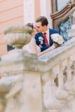 Όμορφο νέο φίλημα γαμήλιων ζευγών στα παλαιά σκαλοπάτια του εκλεκτής ποιότητας κτηρίου Στοκ Φωτογραφίες
