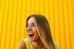 Όμορφο νέο χαμόγελου γυναικών μεγαλοφώνως πέρα από το κίτρινο backgro στοκ εικόνα με δικαίωμα ελεύθερης χρήσης